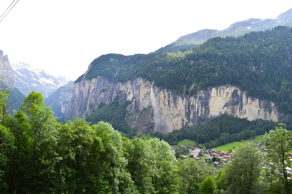 Looking at a distant waterfall falling from cliff in swiss alps