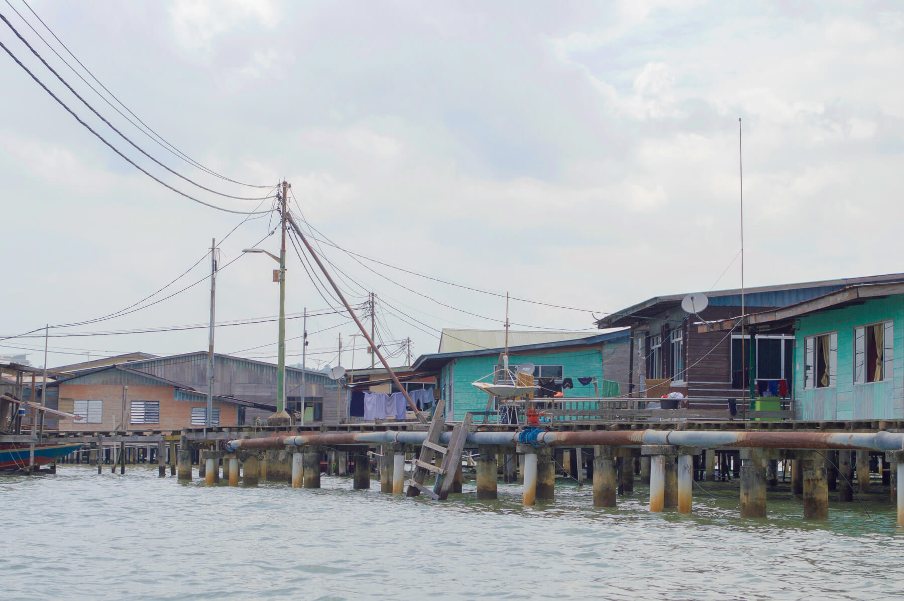 Looking at the Brunei water village from the boat, with the huge pipes and coloured buildings