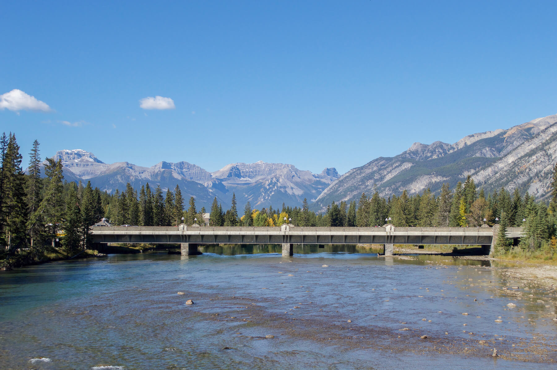 A big wide river flowing under a bridge towards the rocky mountains in Banff