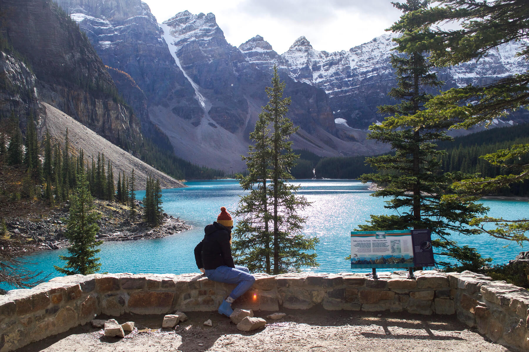 Girl sitting on a stone wall overlooking Moraine Lake