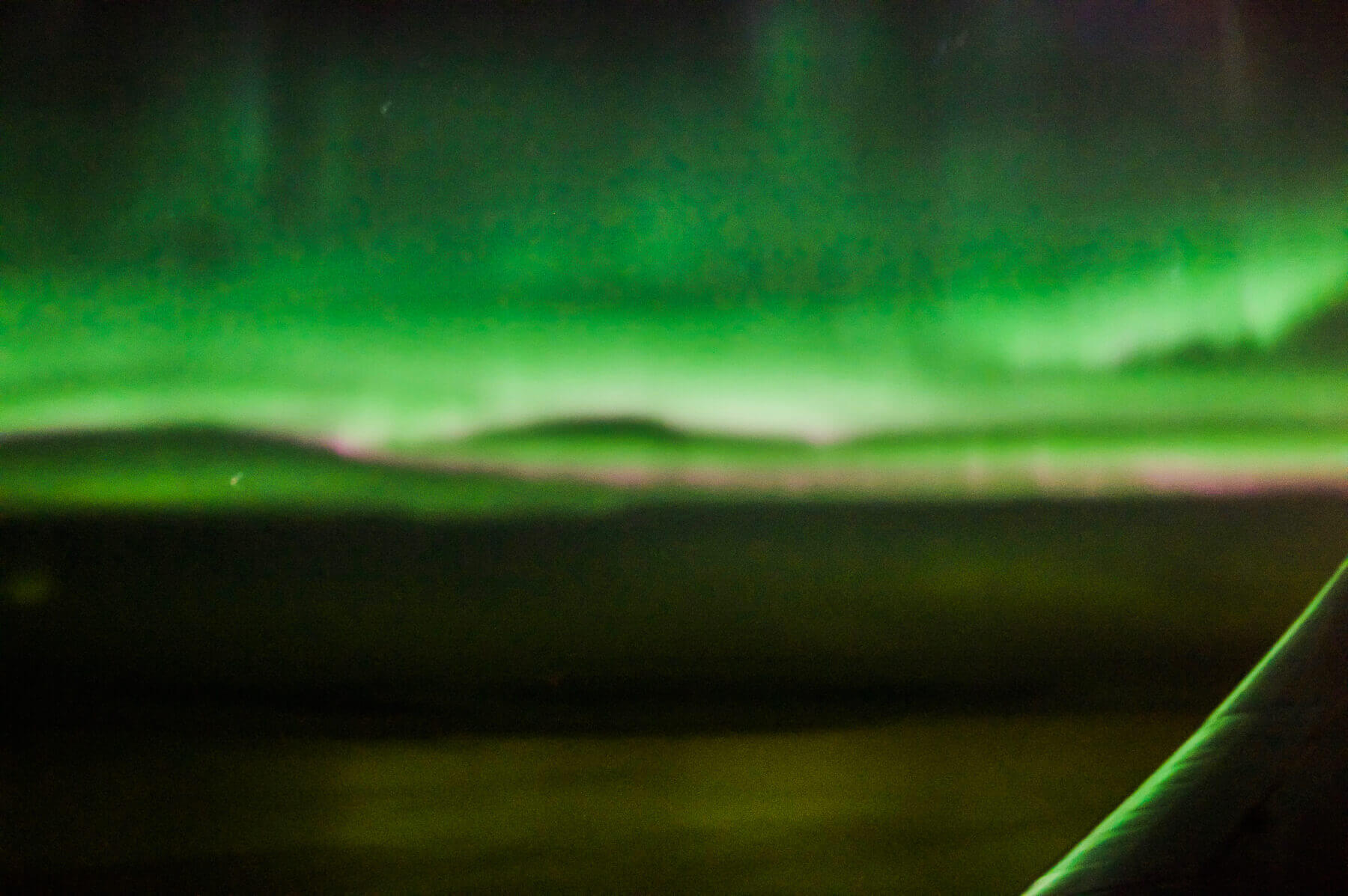 An unfocused image of the Northern Lights over an aeroplane wing