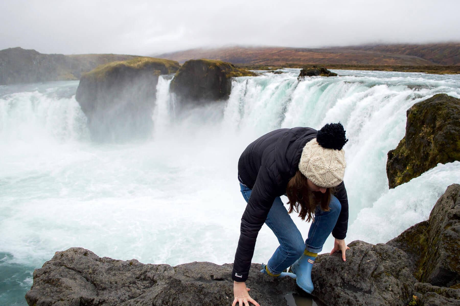 girl on edge of godafoss waterfall