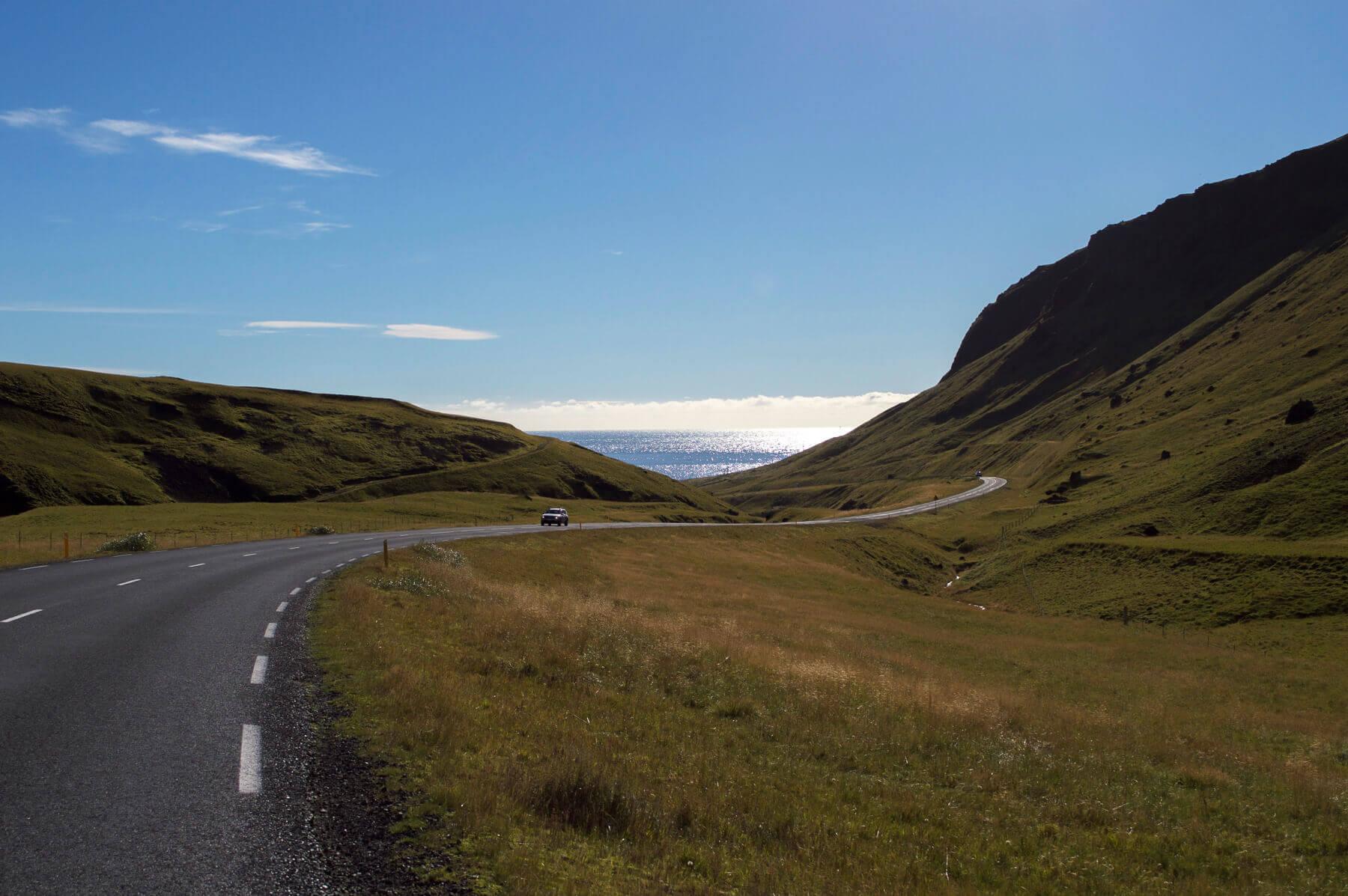Road towards the ocean through a valley
