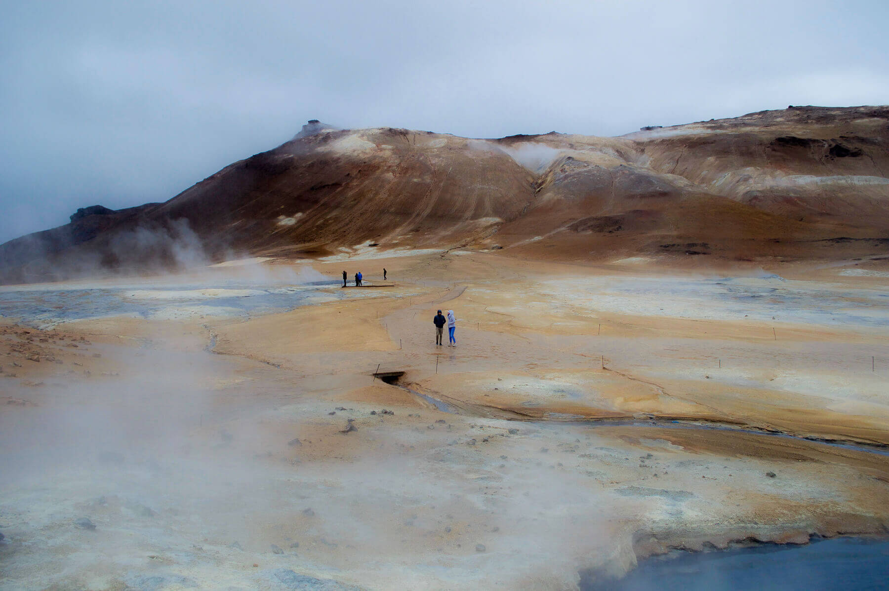 People standing on a geothermal field surrounded by smoke