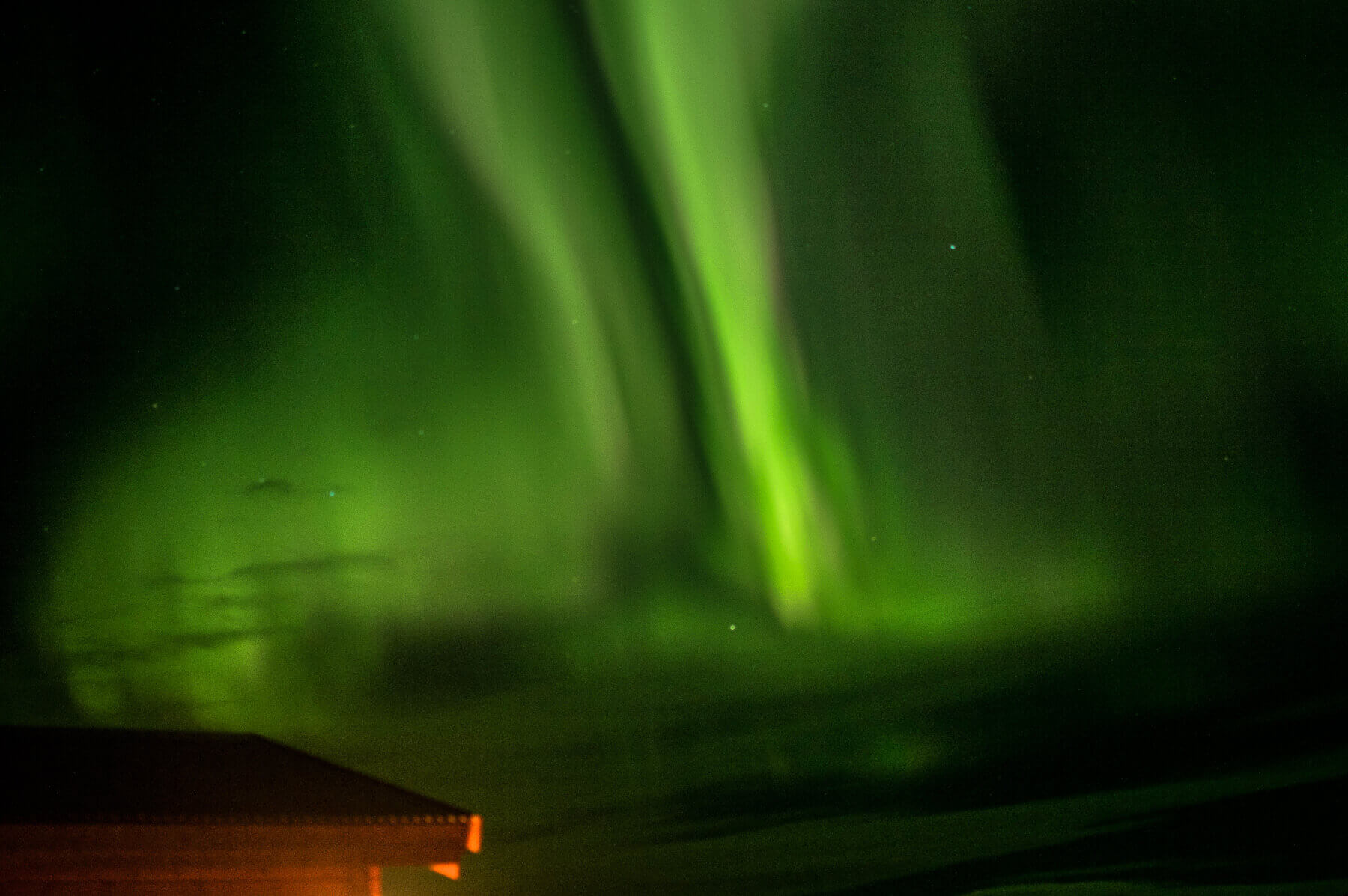 The green aurora borealis above a cabin roof