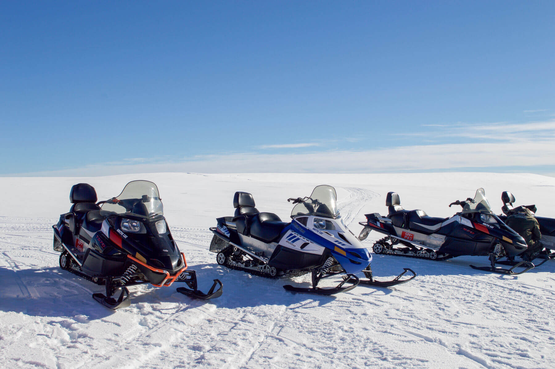 4 snow mobiles on the top of a glacier