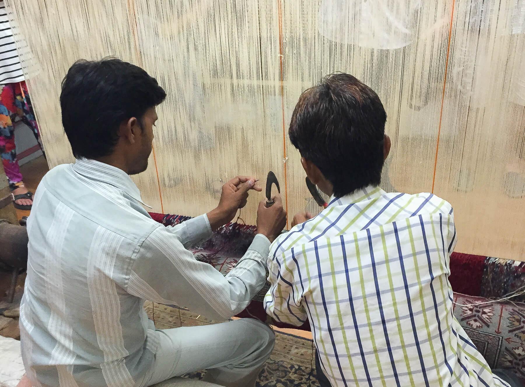 2 Indian men making oriental knot rug