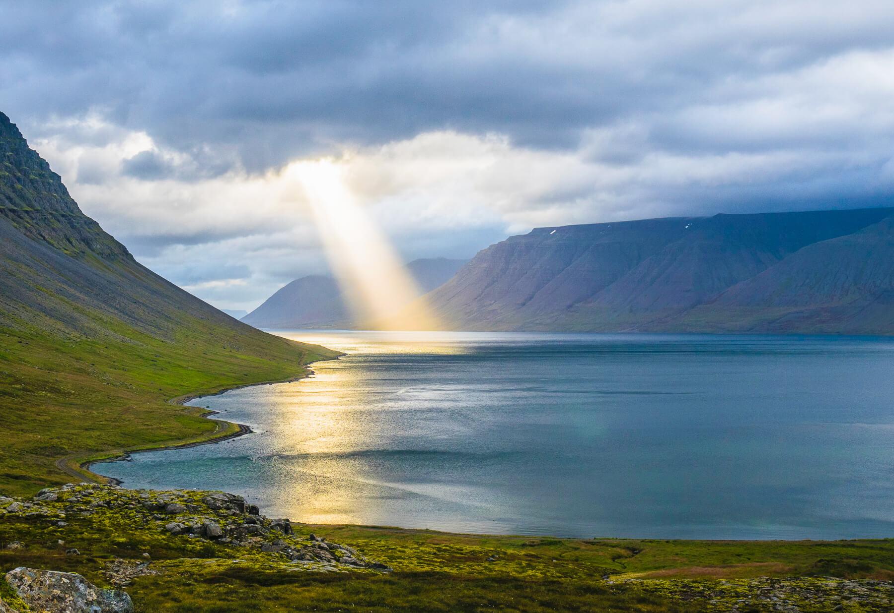 sun shining through clouds onto lake