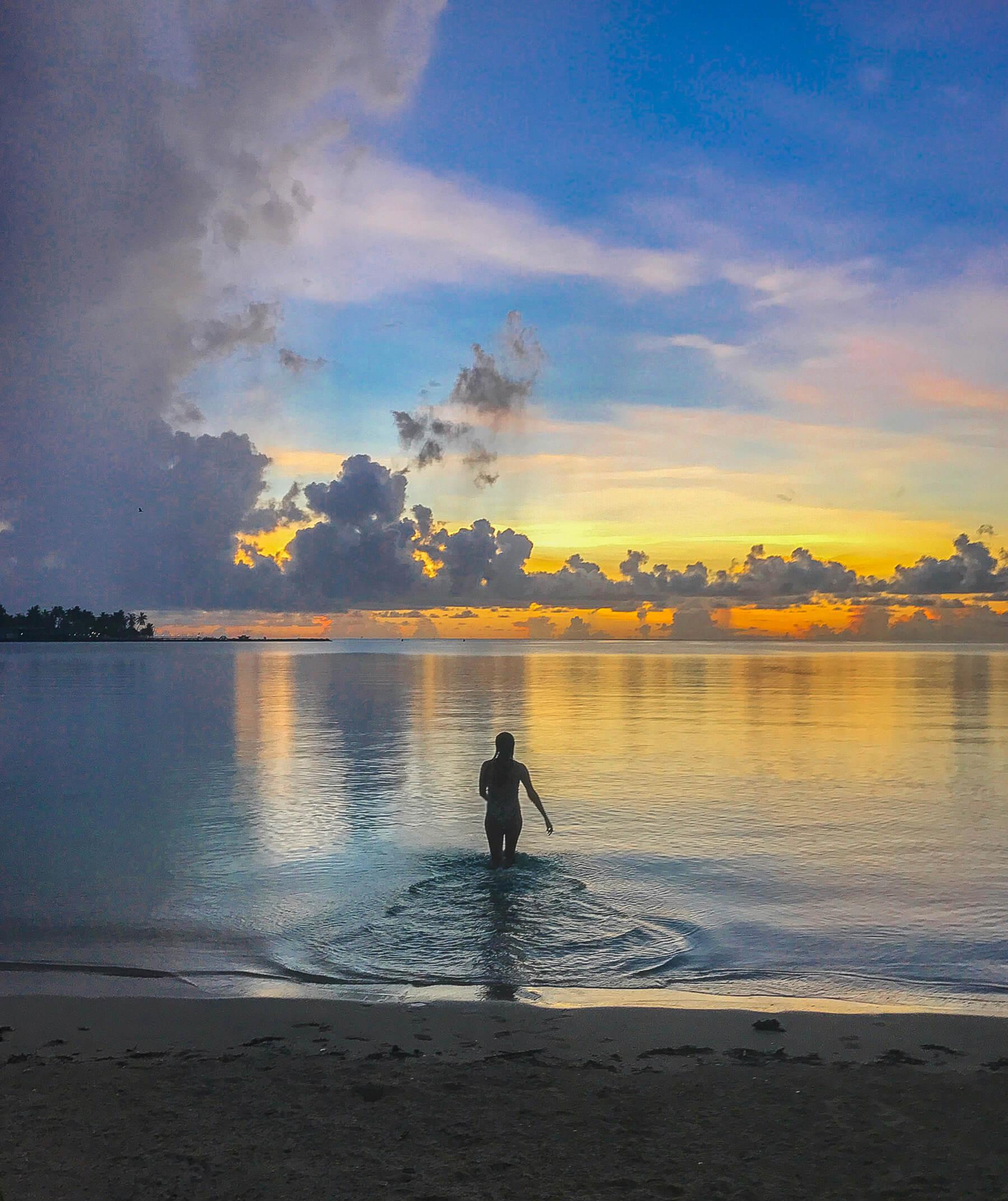 Silhouette of girl walking in ocean towards sunset