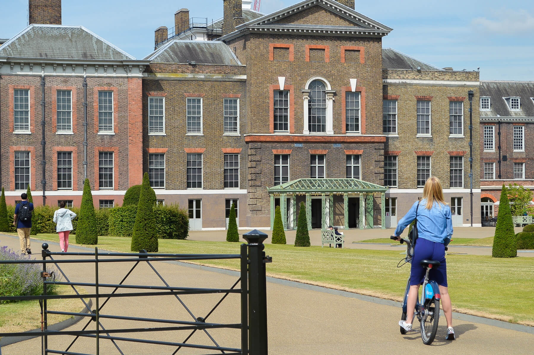 woman on bicycle in garden in front of kensington palace