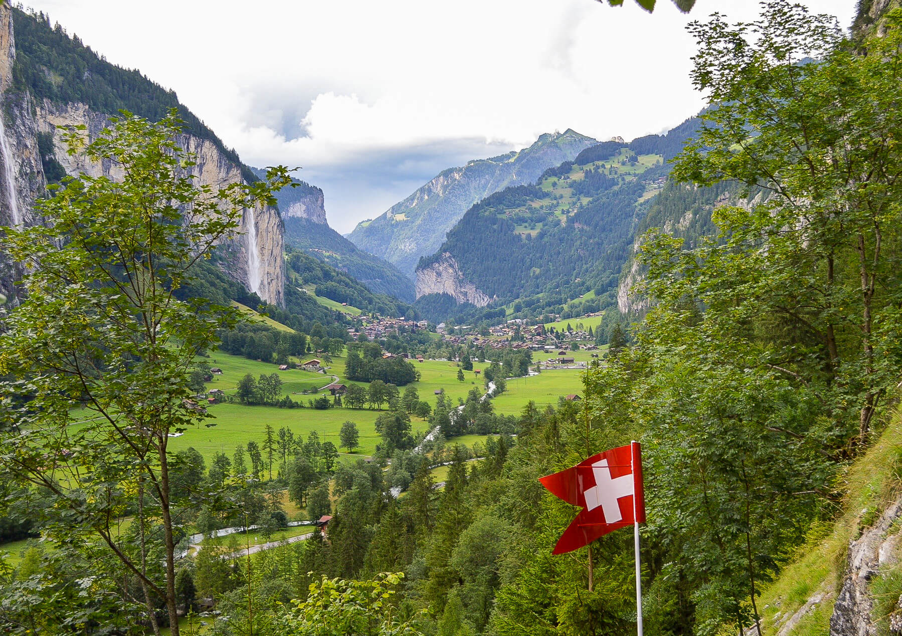 huge valley behind switzerland flag with waterfalls and mountains