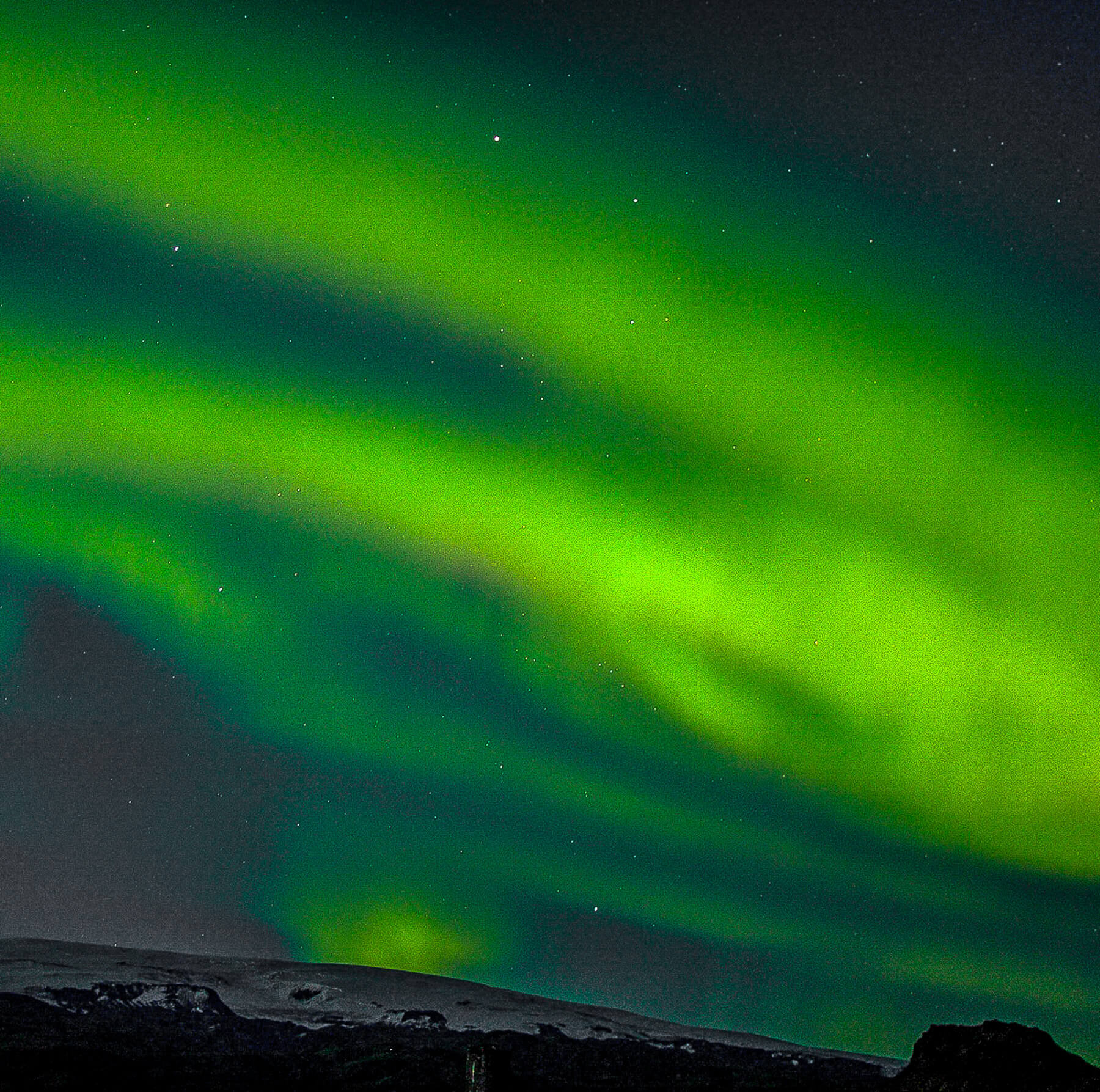 Northern Lights swirling above mountain