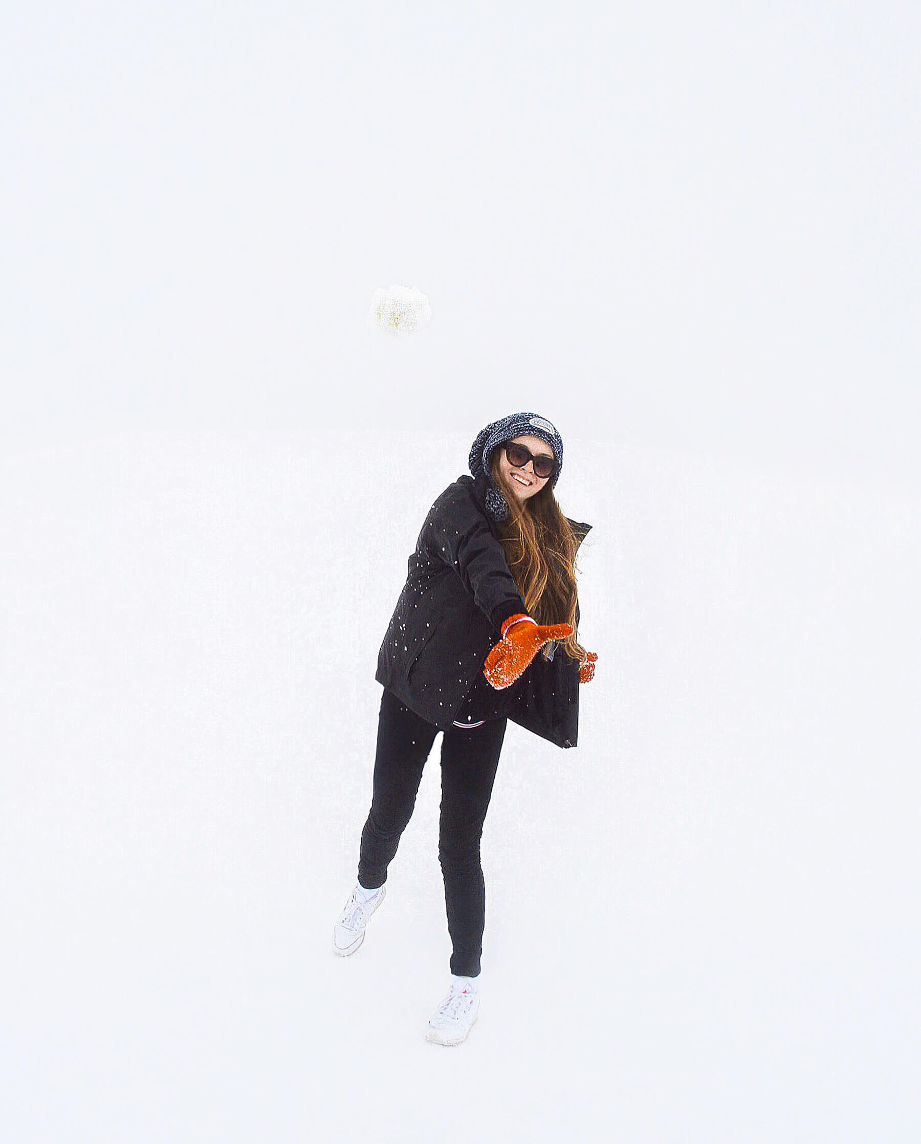 Red haired girl throwing snow ball at the camera