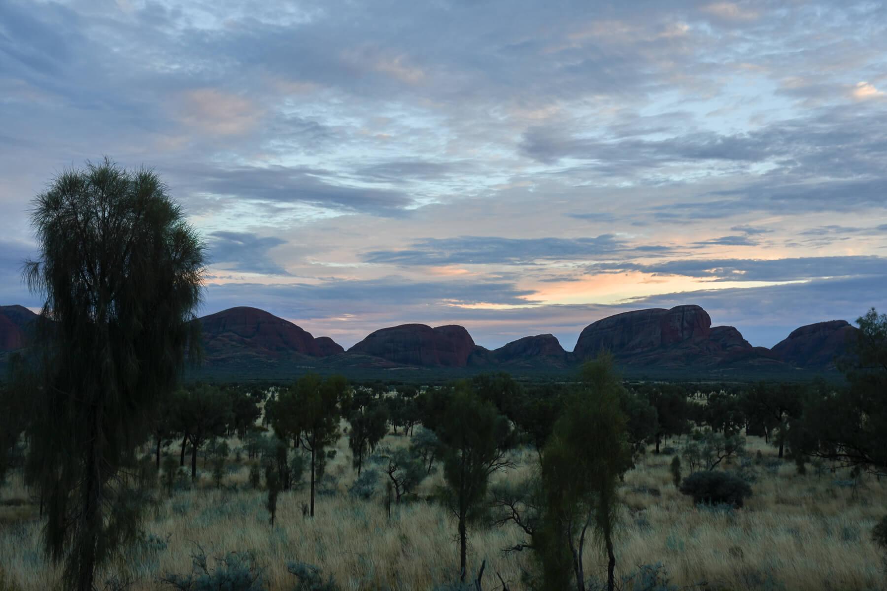 Dull sunrise behind backlit domes of Kata Tjuta
