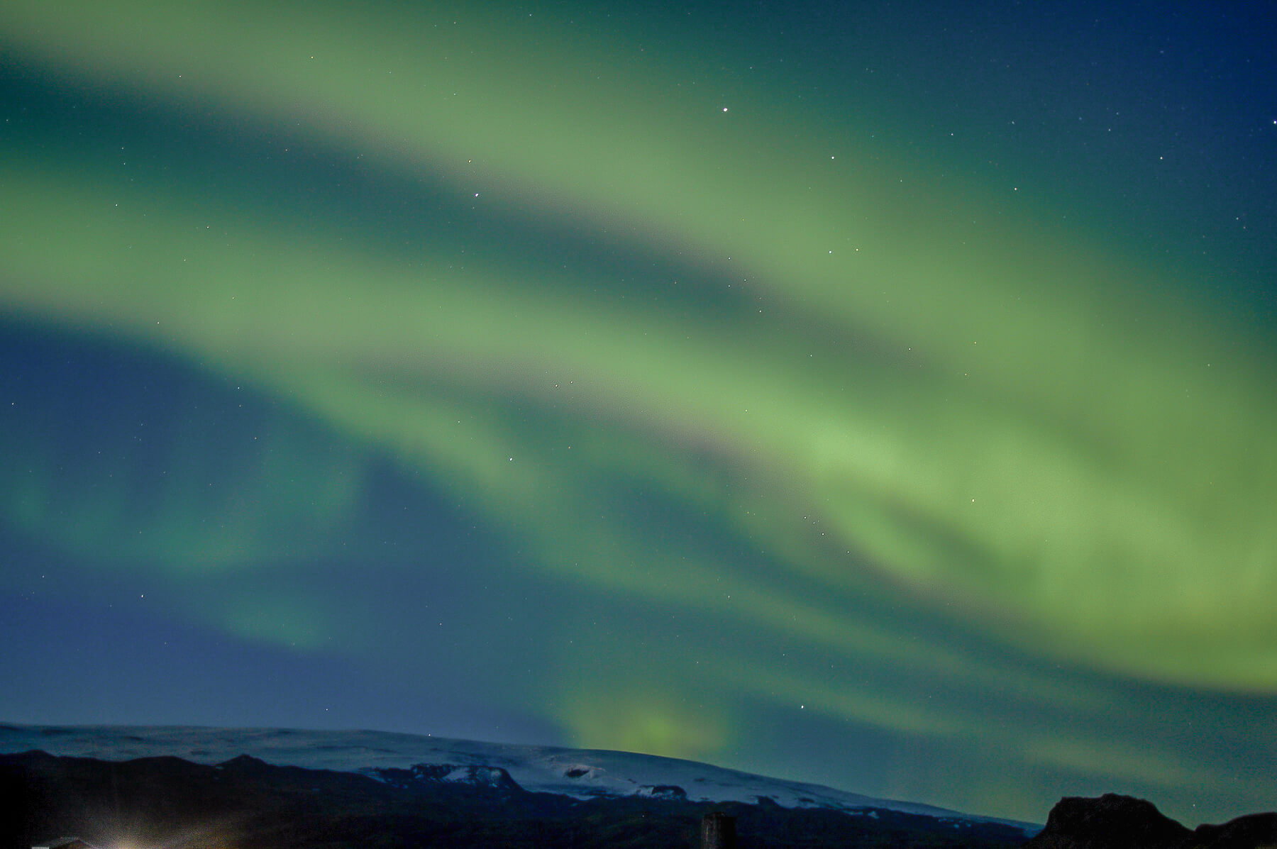 Green and purple Northern Lights dancing across the sky above a Snowy Mountain