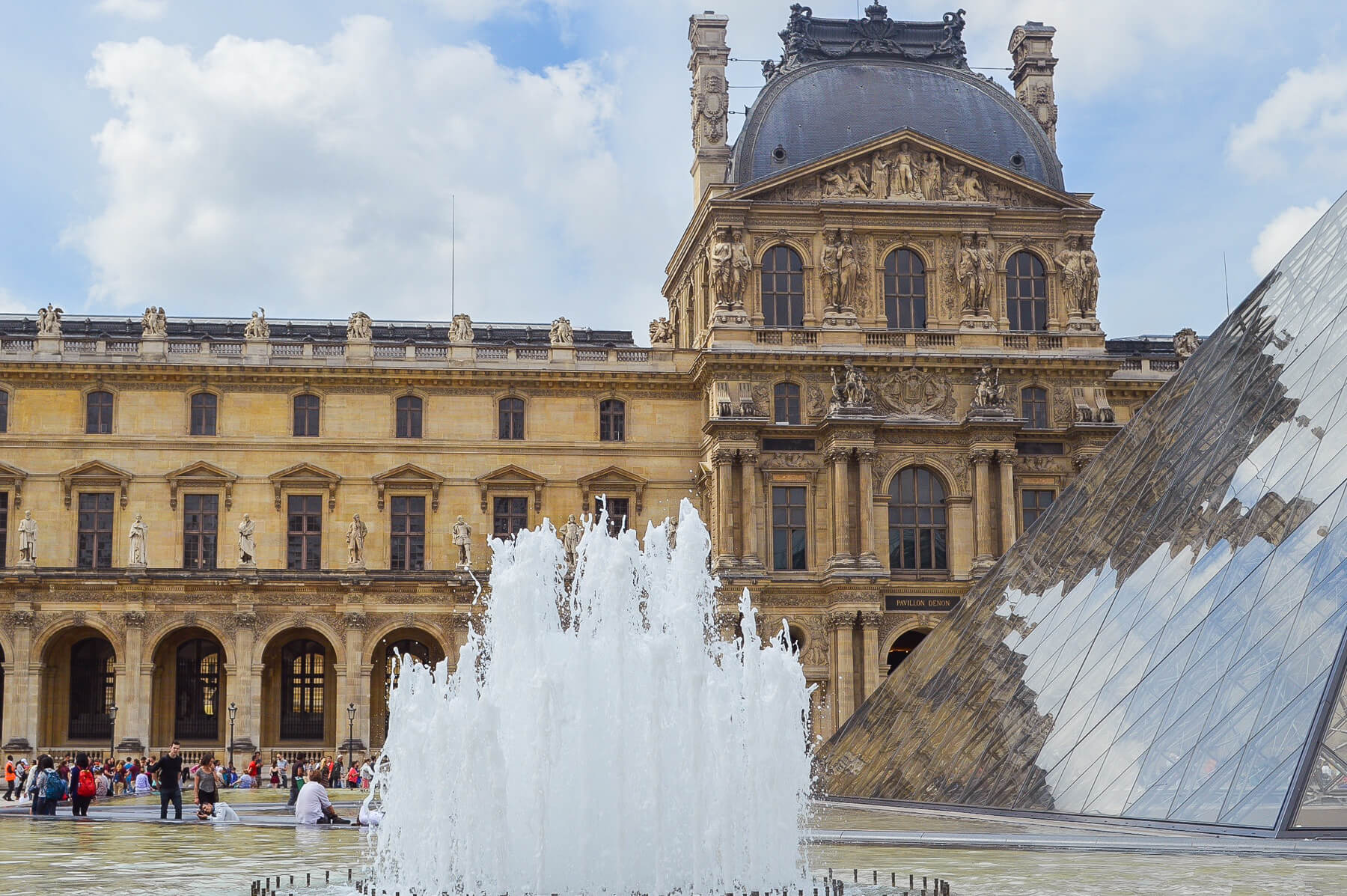 Water fountain display infront of glass pyramid (louvre) and old building