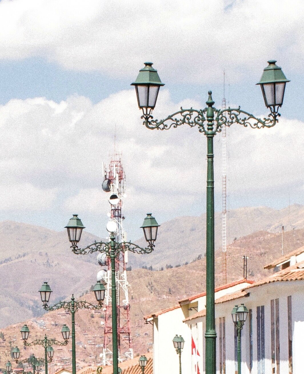 A line of green street lights with the Andes mountains in the background
