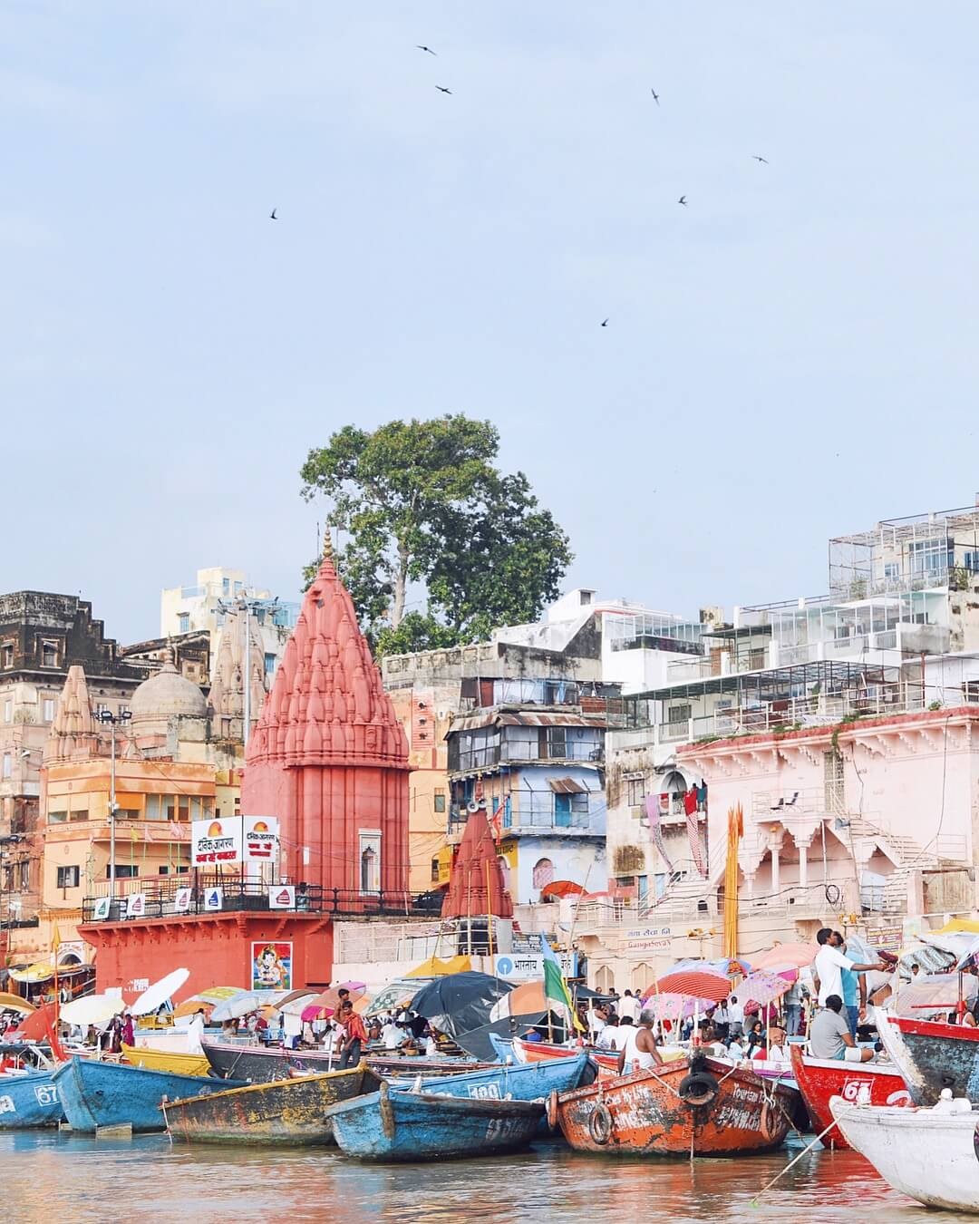 Colourful buildings on a river bank, with bright boats and lots of people on the river - India