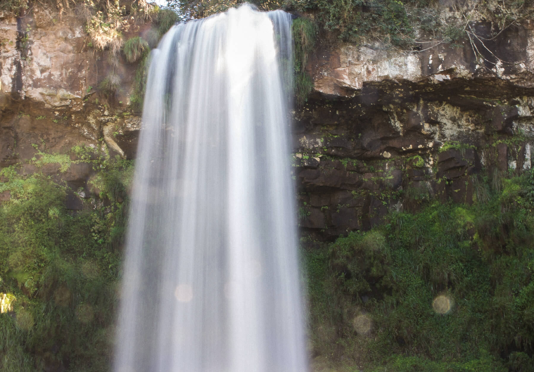 A waterfall falling from a cliff on the forest - Long shutter speed caused water to be very silky