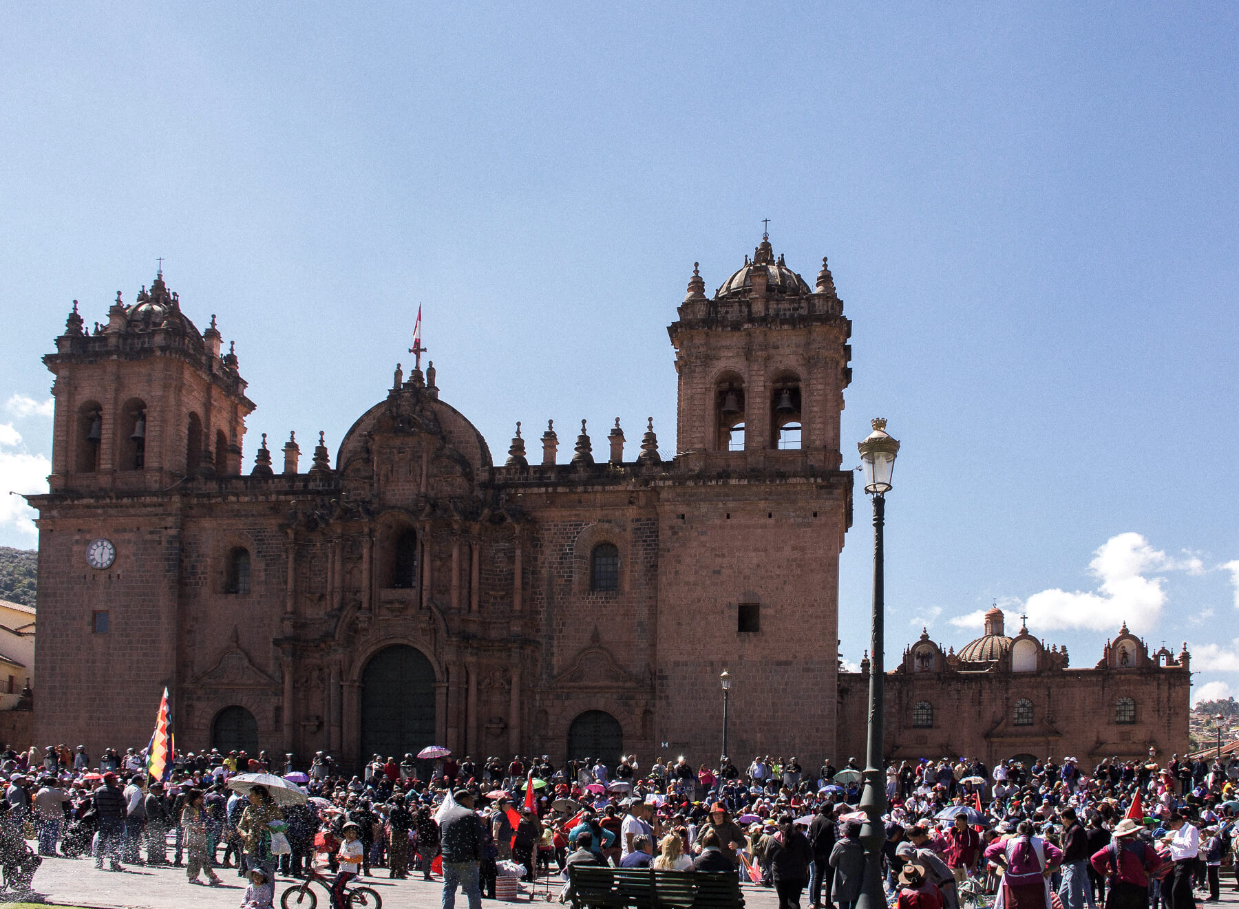 The main square of Cusco with a church and a lot of people surrounding during a protest