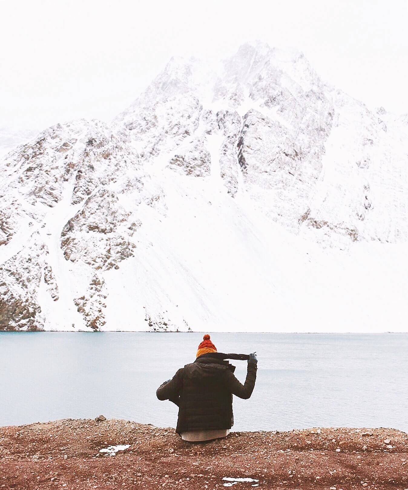 Person in red hat facing away from camera - sitting on edge of cliff and taking off her scarf - infront of mountain and lake