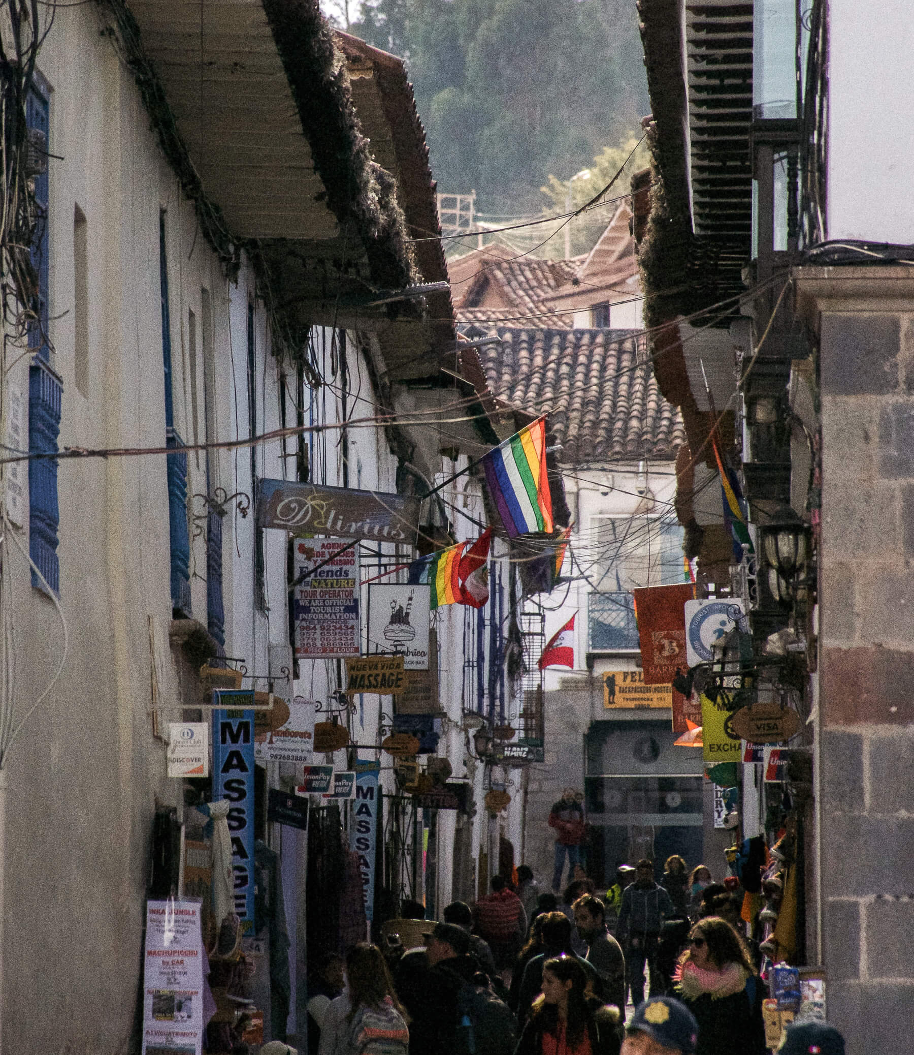 Looking down a small alleyway with signs and flags sticking out from the walls
