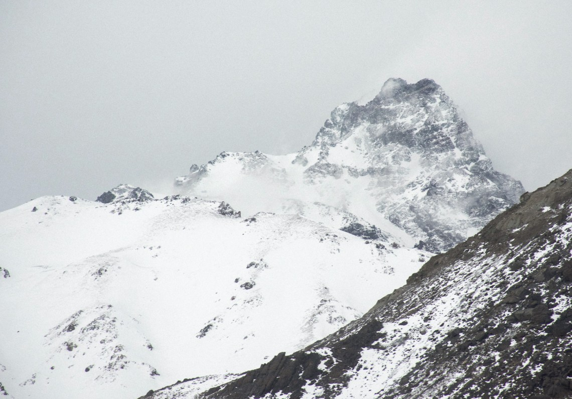 Foggy, ruggeds mountain peak above covered in snow