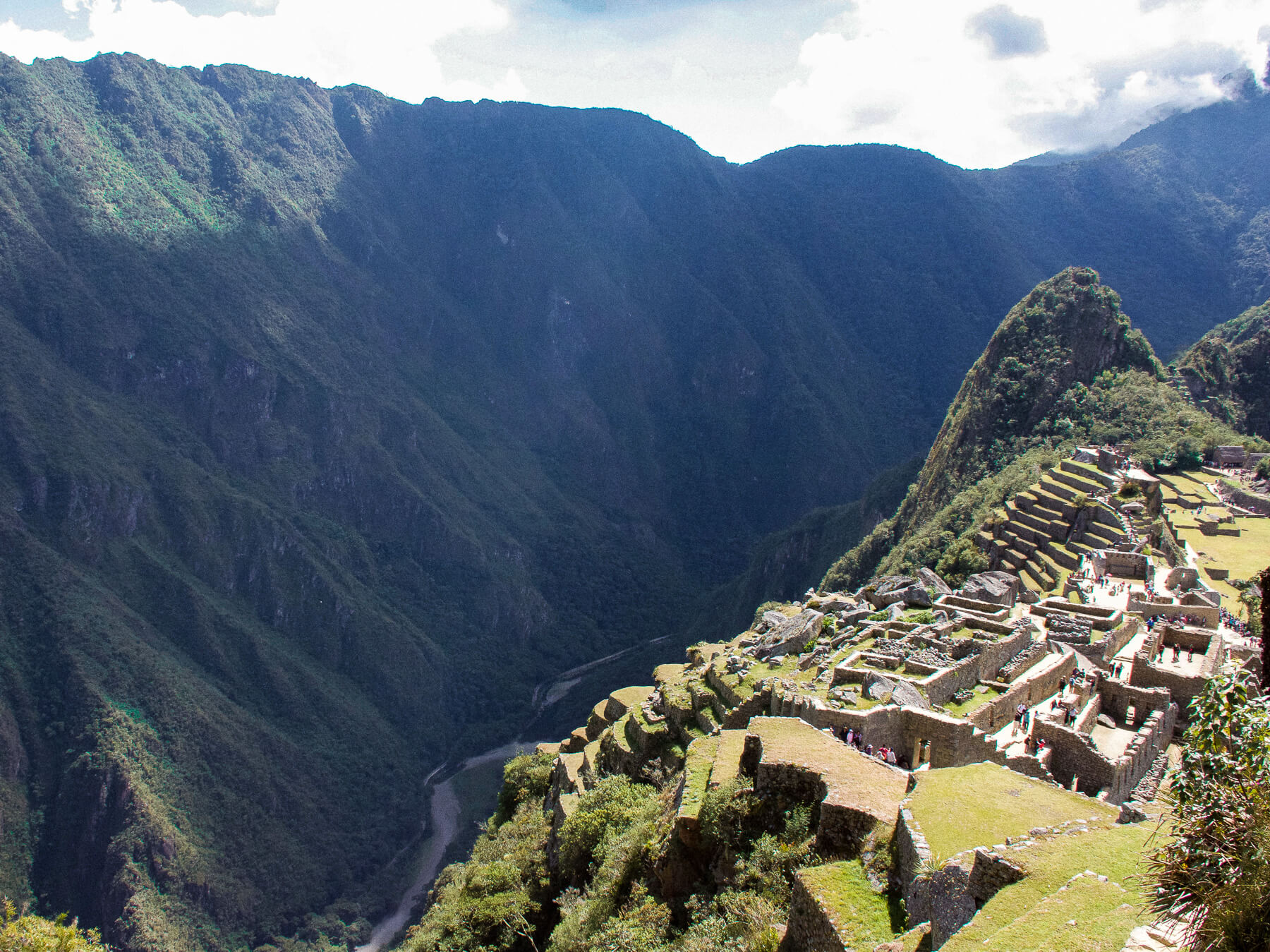 Machu Picchu at the side of the image with a huge valley and river to the left