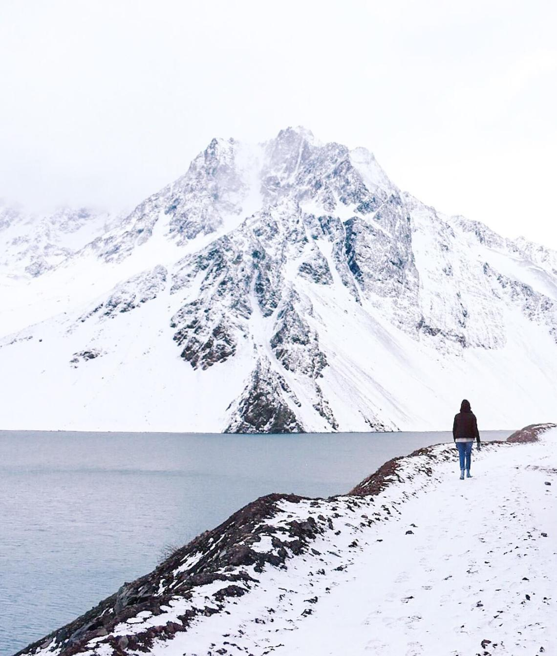 Person wearing black jacket walking through a snowy path with blue reservoir and mountain peak to her left side