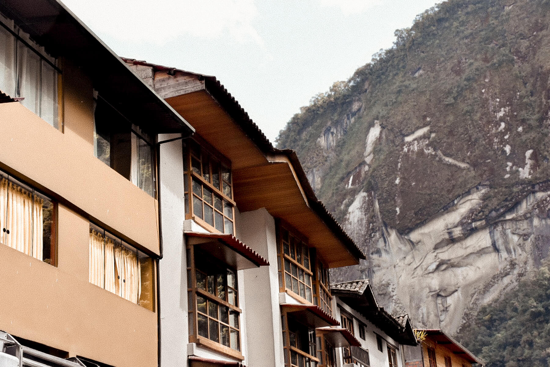Beautiful Peruvian buildings with a cliff face behind them
