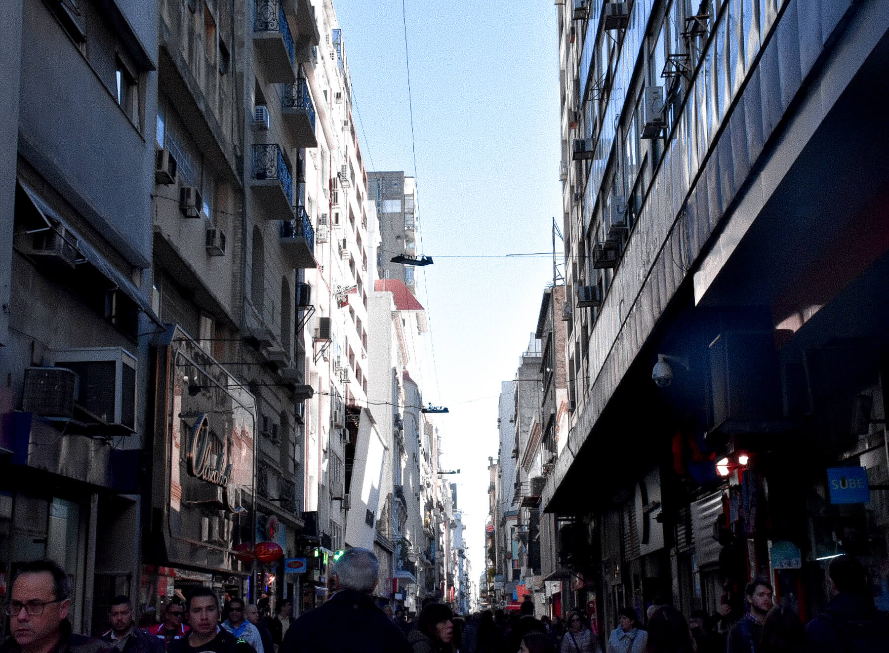 Looking down the road of a busy street in Buenos Aires with lots of people walking