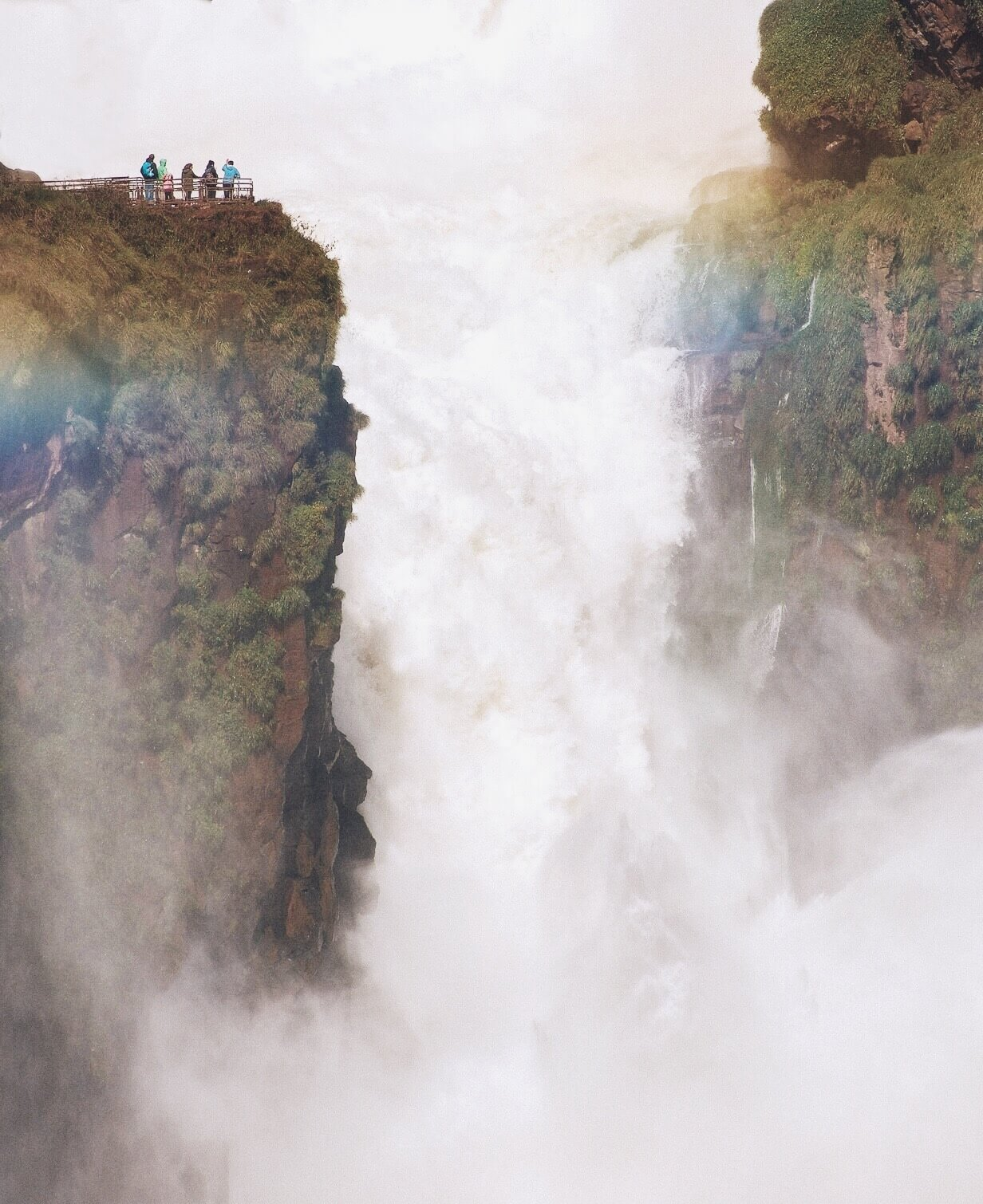 A huge, powerful waterfall with a large group of people standing on a platform directly next to it