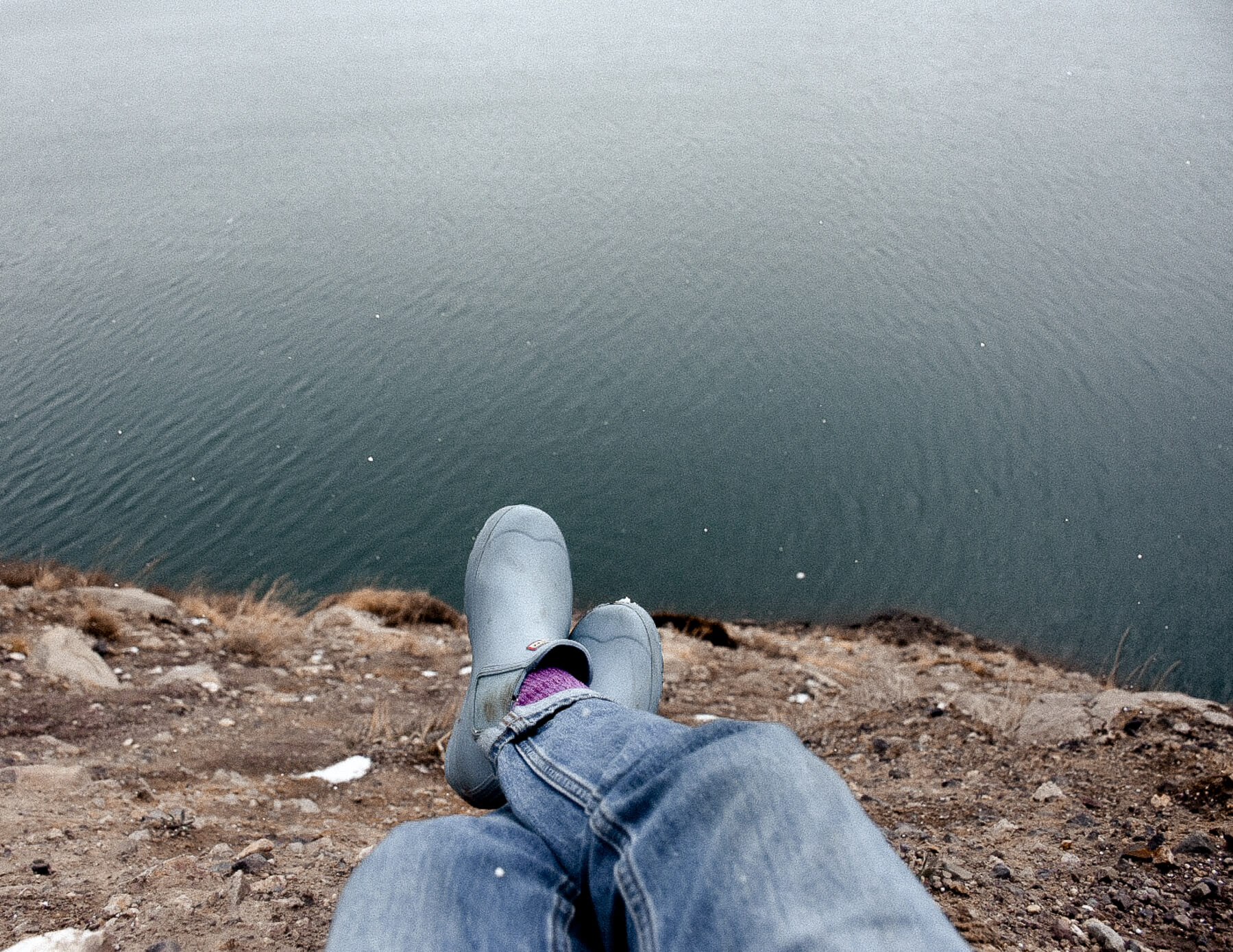 Blue gumboots hanging over the edge of a cliff above a lake