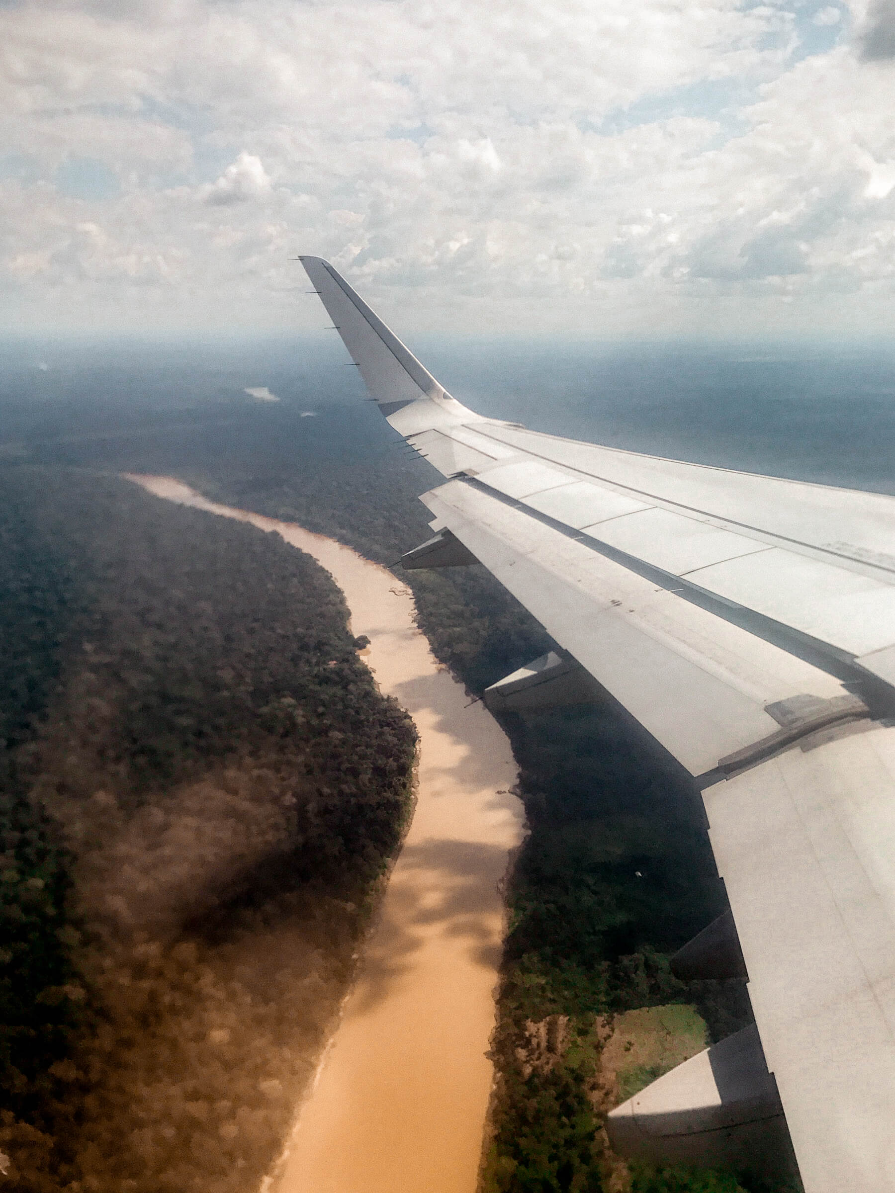 The wing of an aeroplane flying above the Amazon Rainforest and Amazon River