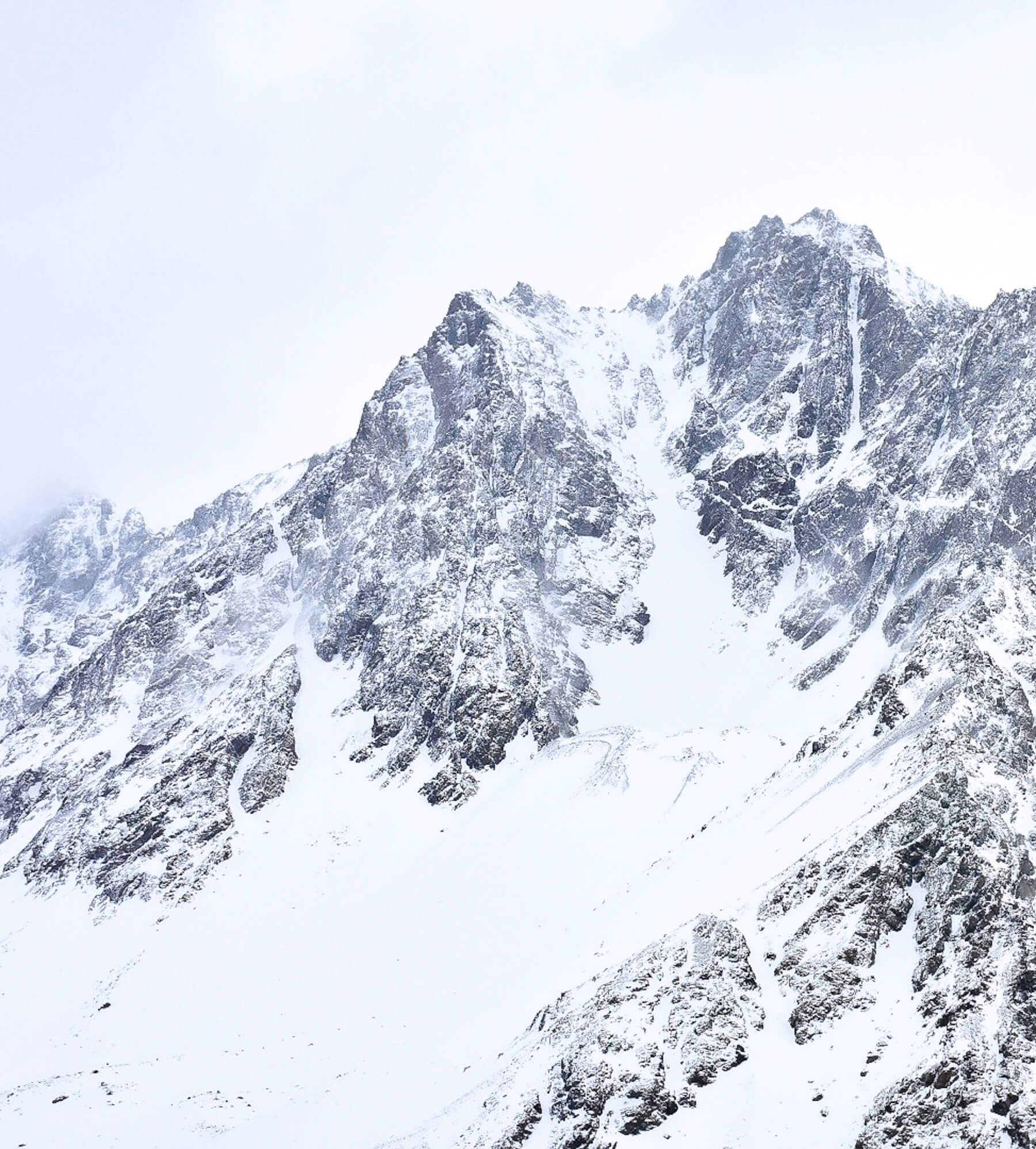 The rocky Andes Mountain peak covered in snow