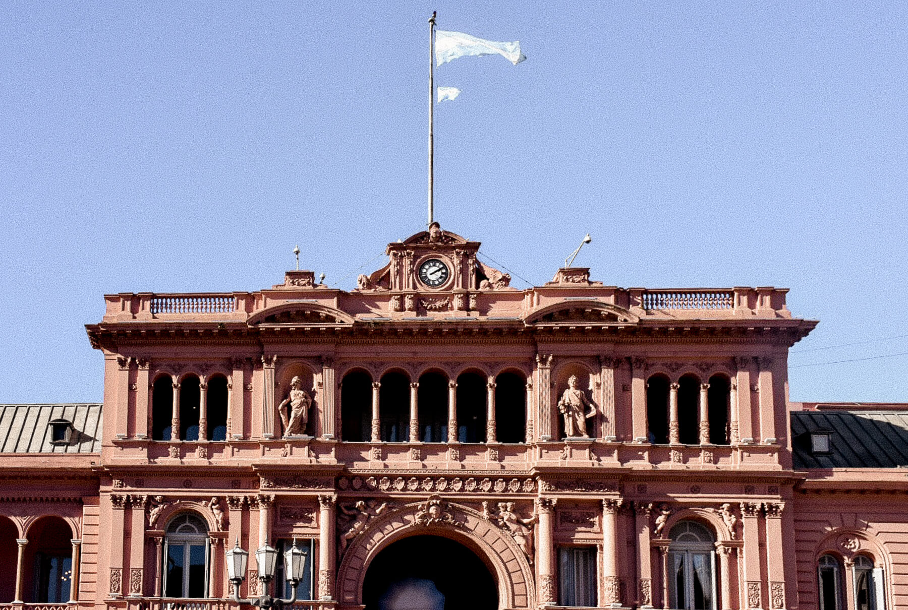 A terra cotter coloured parliament building with the Argentina flag waving above it