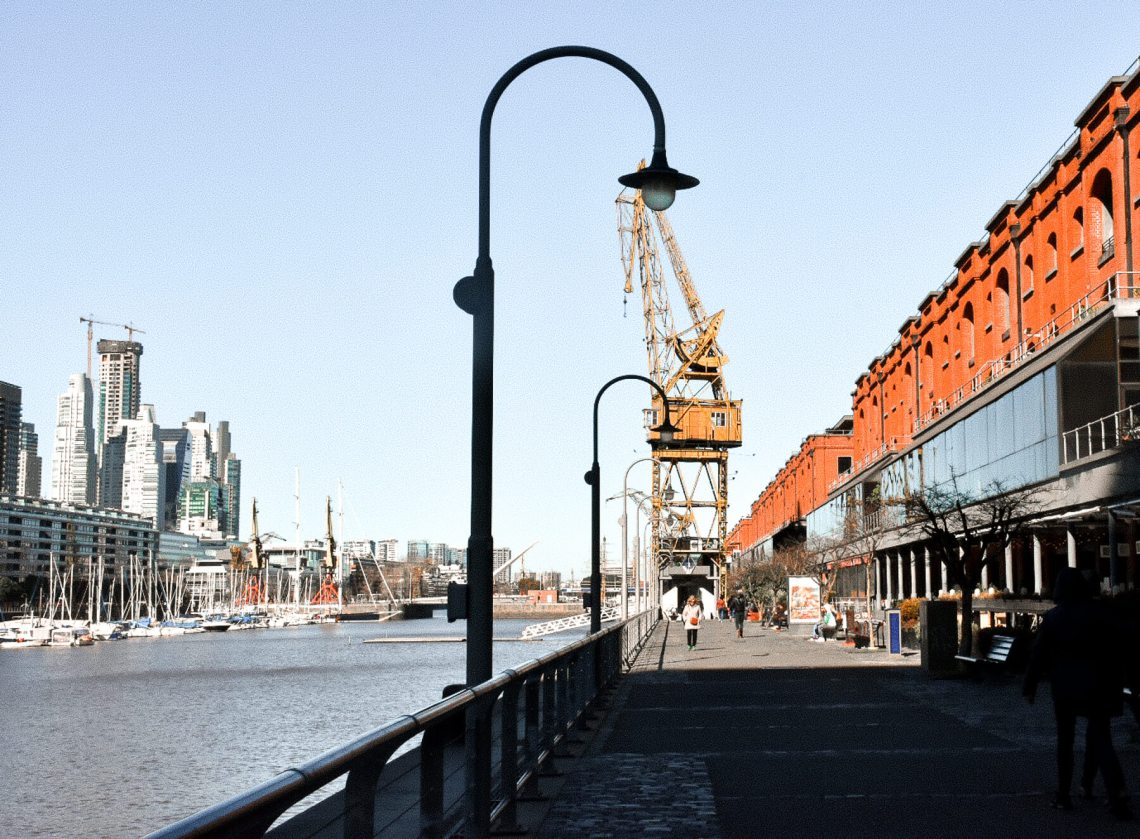 The inlet that runs through Buenos Aires, with old buildings, a huge yellow crane and arched light posts along the walkway