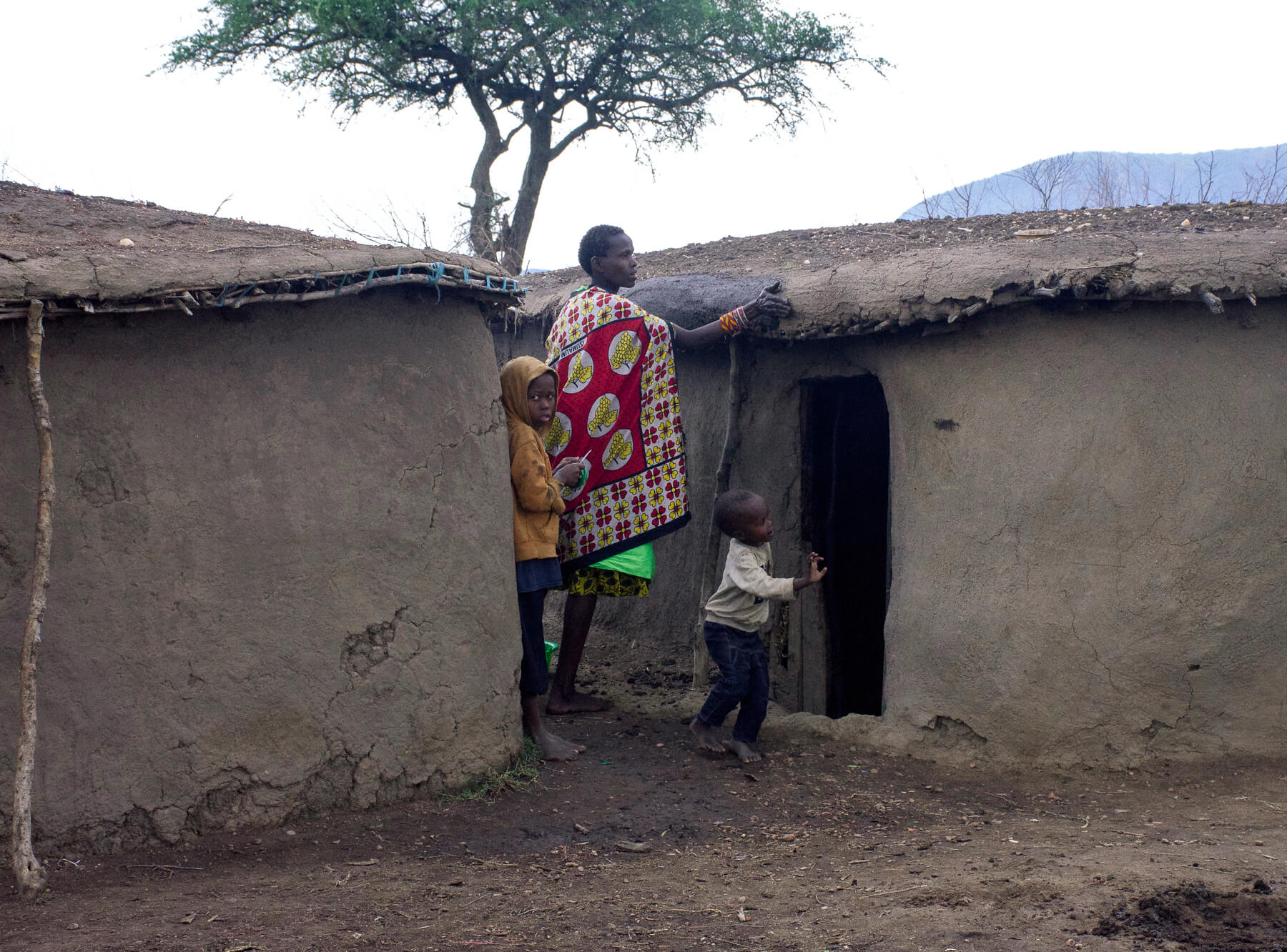 A mother in a Maasai village fixing her house with mud, with her children helping too