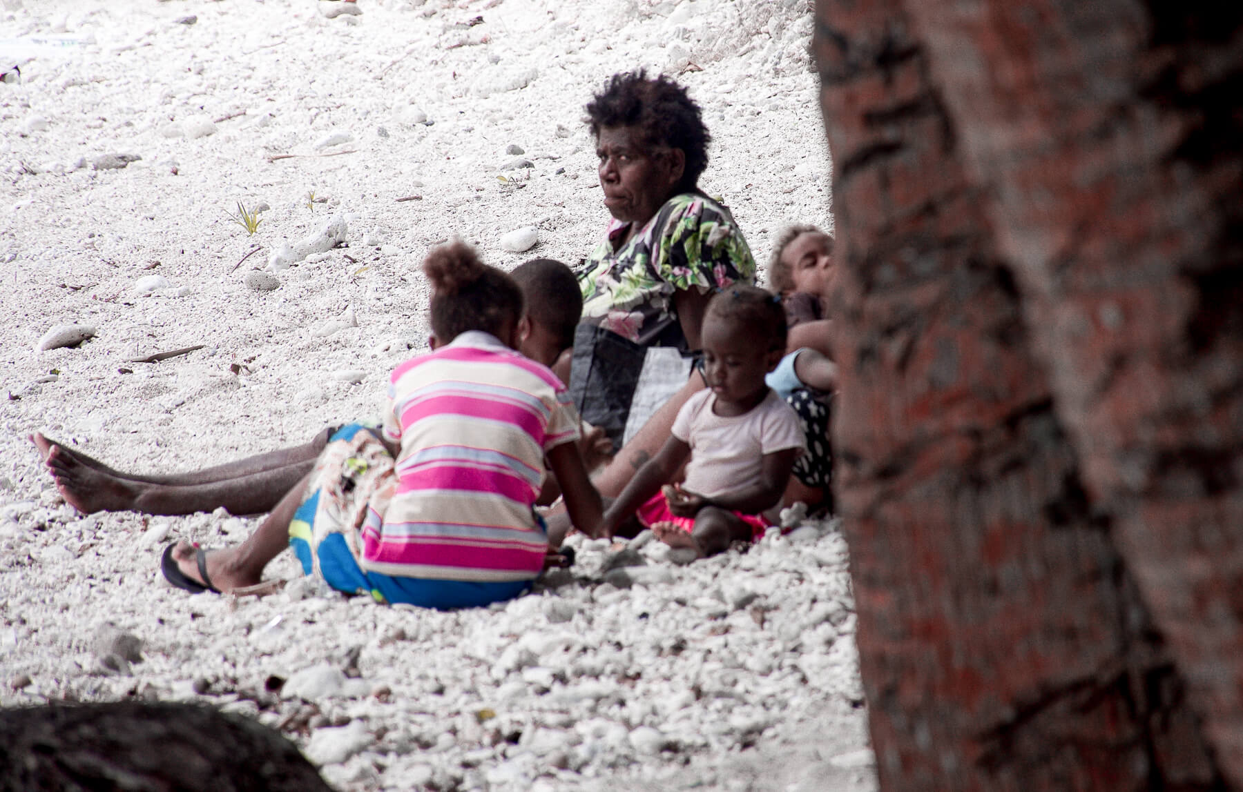 A local Vanuatu family (mother and 4 children) relaxing on the beach
