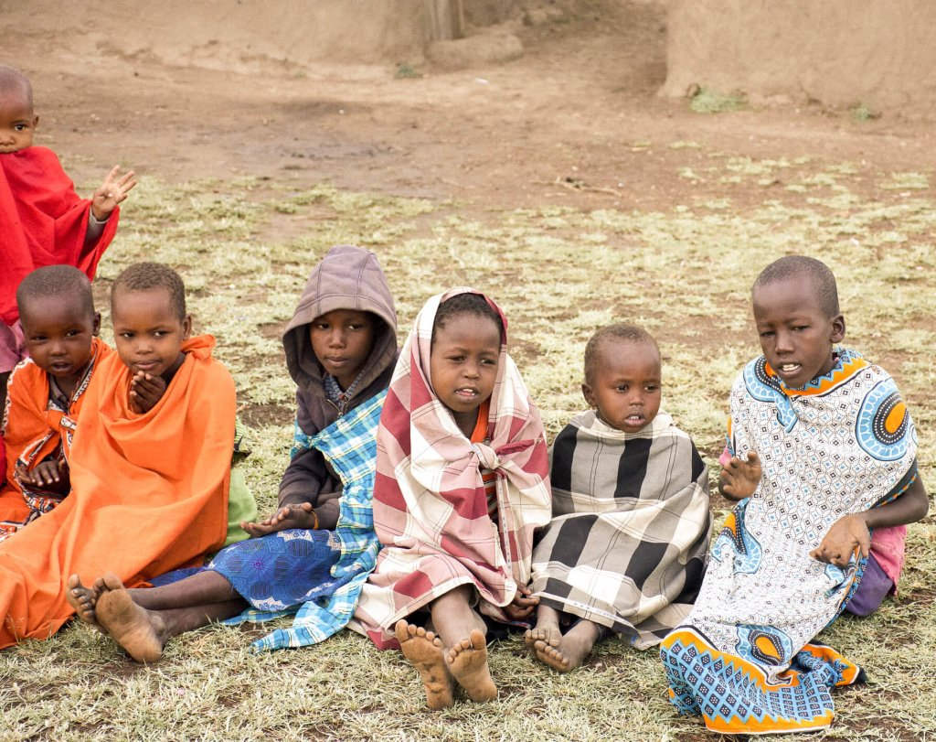 7 Maasai children sitting on the grass singing a traditional song