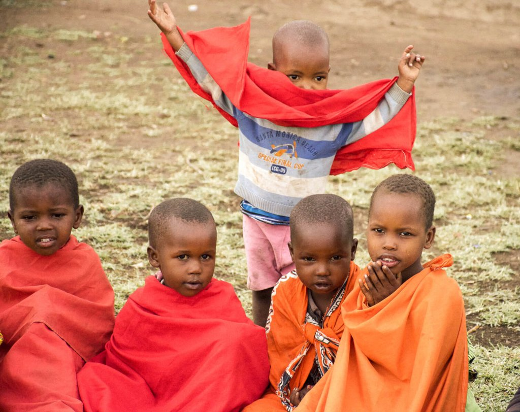 Young kenyan children from the Maasai tribe sitting on the grass, with one young boy throwing his hands up behind them