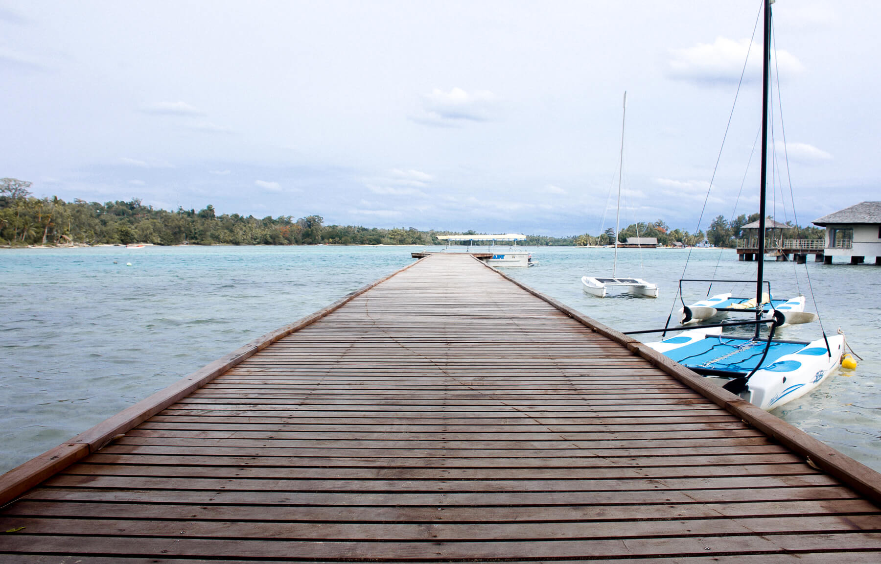 Looking down a pier on the lagoon with boats surrounding it