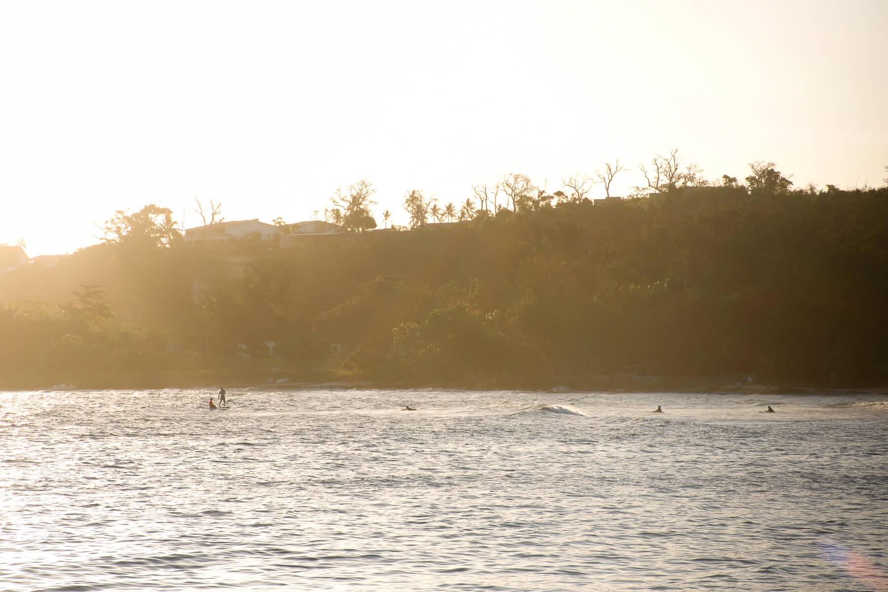 Watching Vanuatu locals surfing in the ocean during golden hour