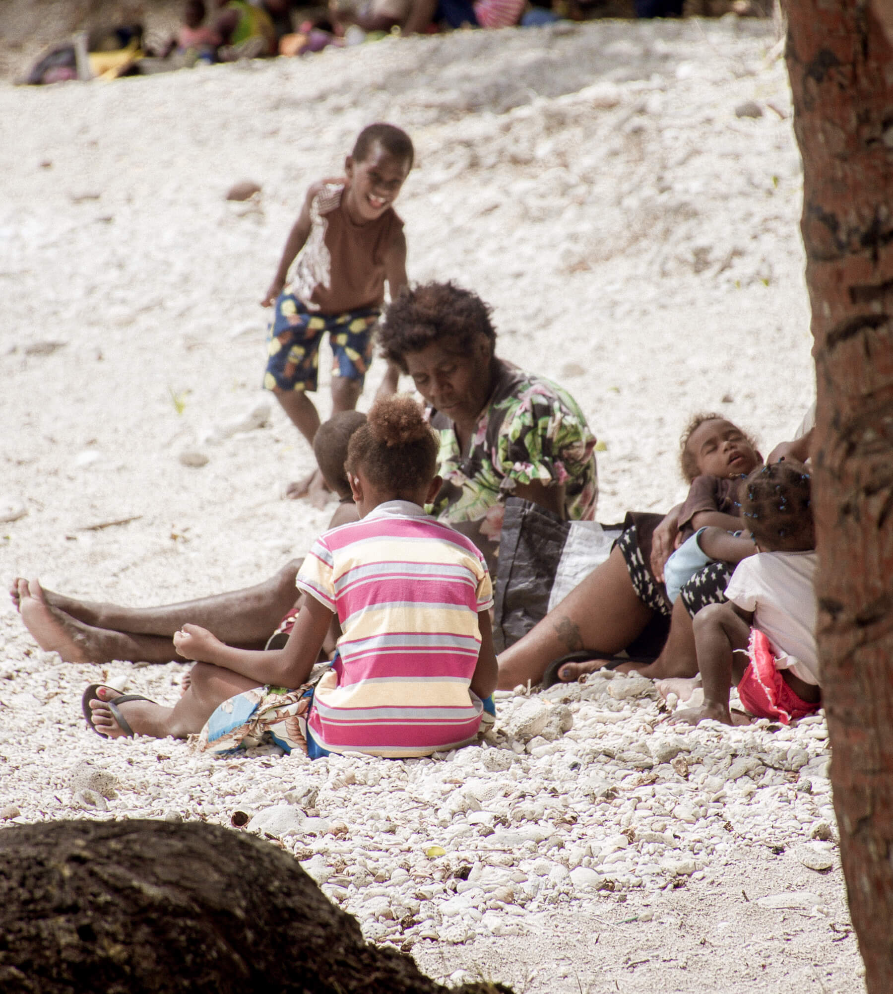 A family of local Vanuatu people sitting on a beach - a mother and her sleeping baby and 3 happy children