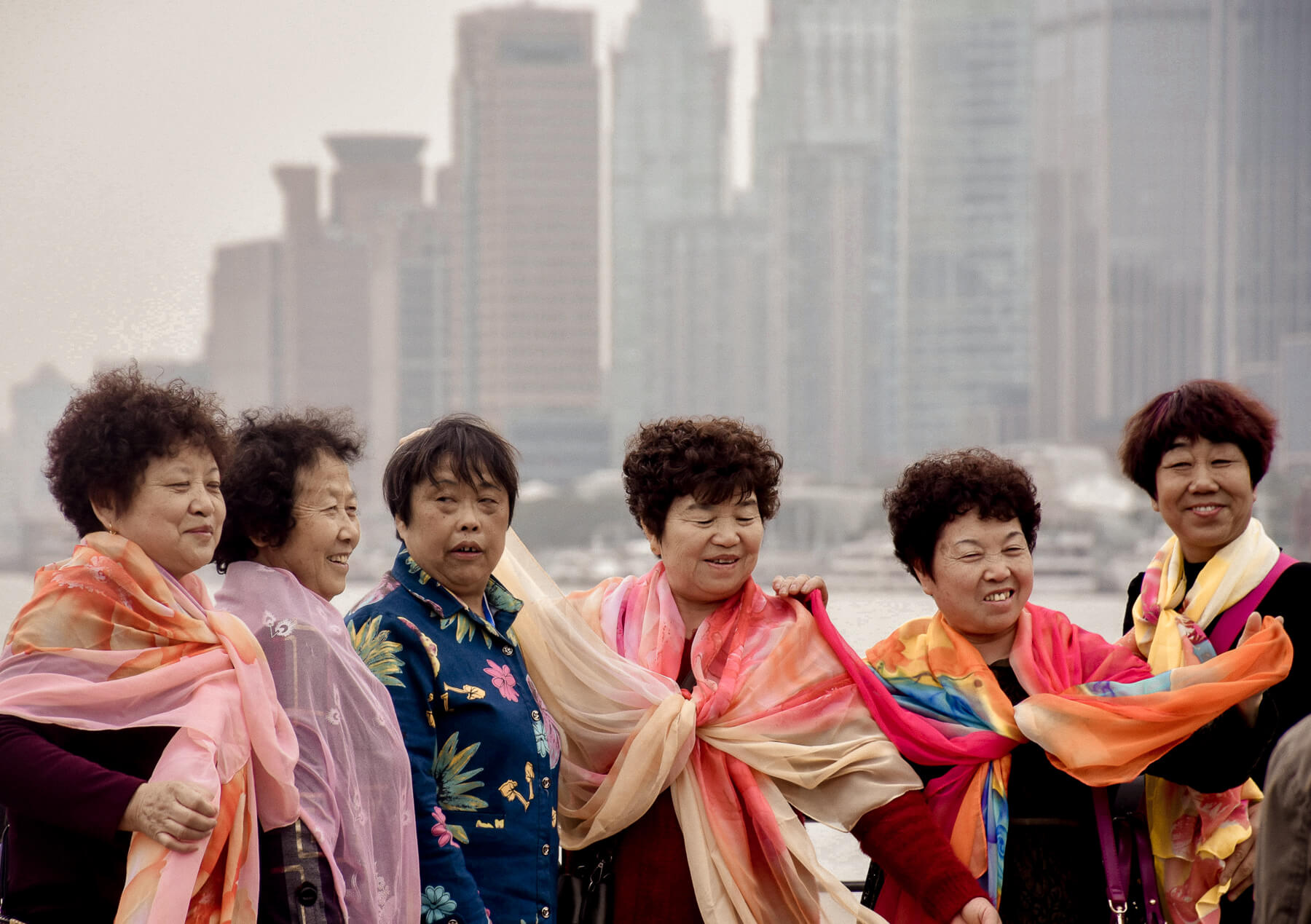 A group of 6 elderly Chinese ladies posing in front of the Bund in Shanghai - All wearing colourful scarfs.