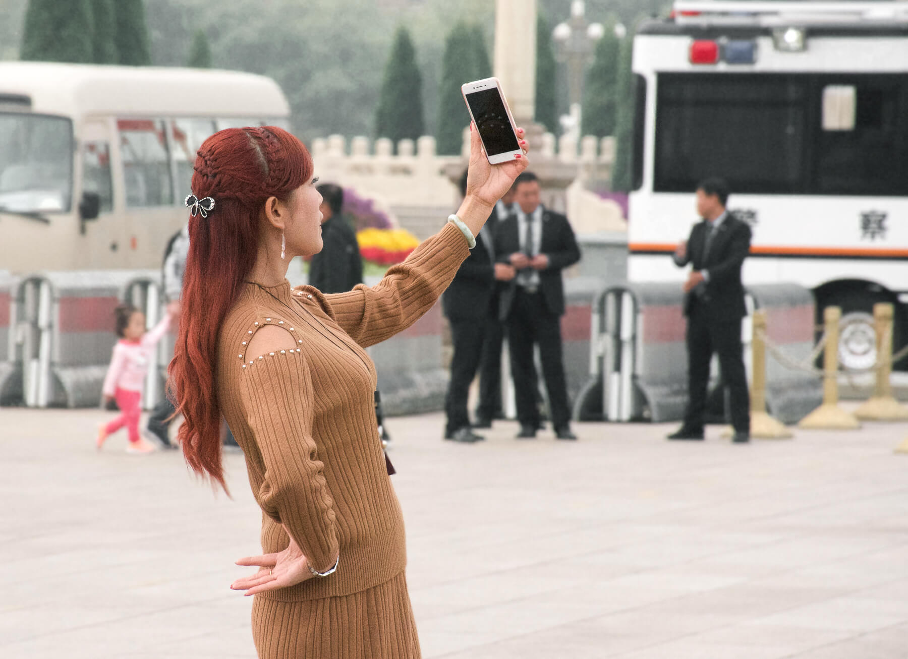 A Chinese lady with long red hair, holding her phone up high taking a selfie