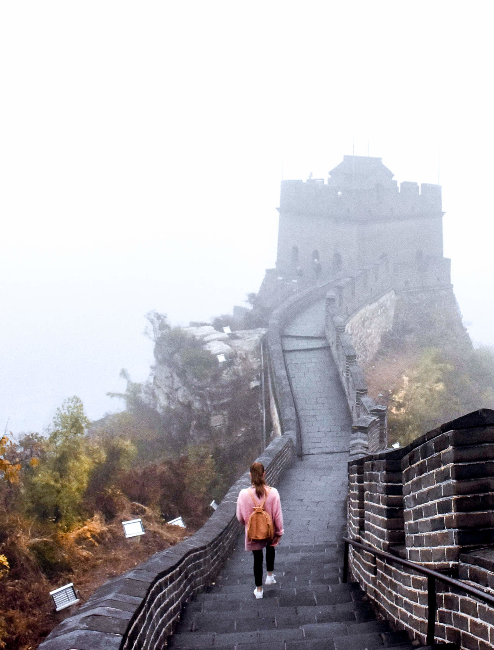A girl in a pink jumper walking the Great Wall of China, high up in the fog