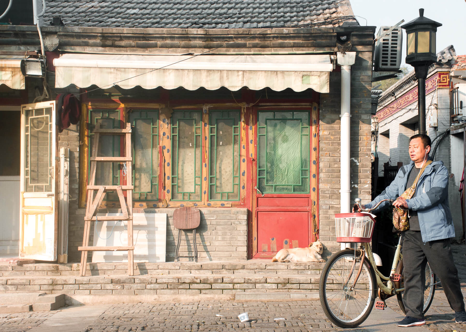 A Chinese man pushing his bicycle in front of an old building with a dog sleeping on the front porch