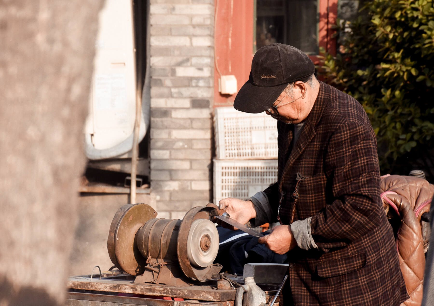 A man carving a knife on the street with an old machine in Beijing