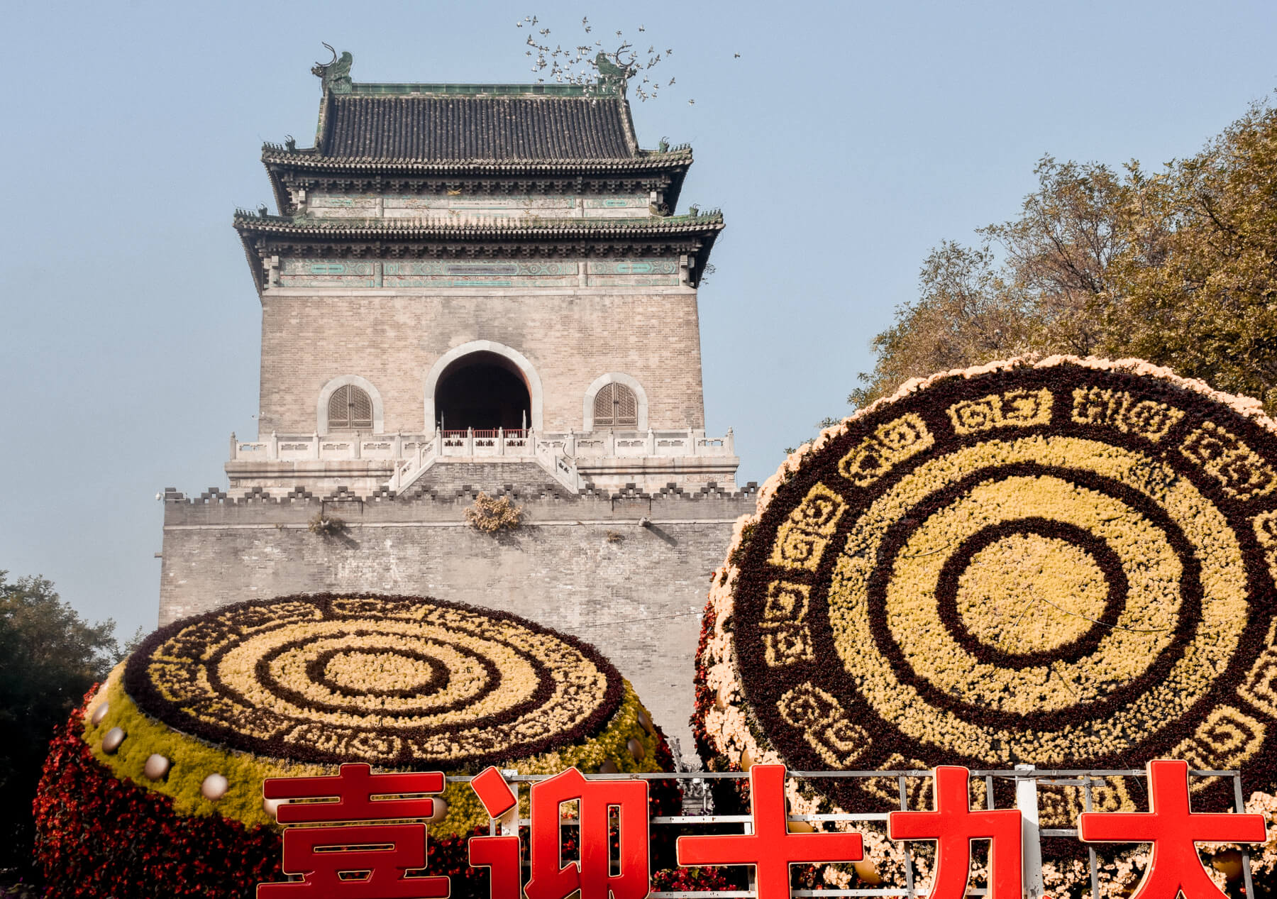 Amazing flower display in front of a bell tower in Hutong, with homing pigeons flying above it